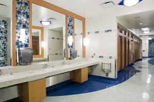 At YVR, travellers find clean, modern washrooms in which to freshen up during their journeys. The washroom walls in C-Pier of the Domestic Terminal are covered in shades of blue, red, and yellow mosaic tiles. Wave-shaped blue flooring winds down the curved corridor, leading guests to their choice of bathroom stalls.