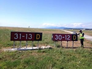 A Vancouver Airport Authority employee replacing the 30-12 crosswind runway sign with a new 13-31 sign to reflect the realigment of the runway with the shifting magnetic heading.